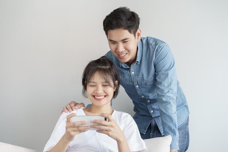 Les jeunes heureux aiment les couples asiatiques se reposant sur le divan ? la maison, regardant le t?l?phone portable, les jeune image stock