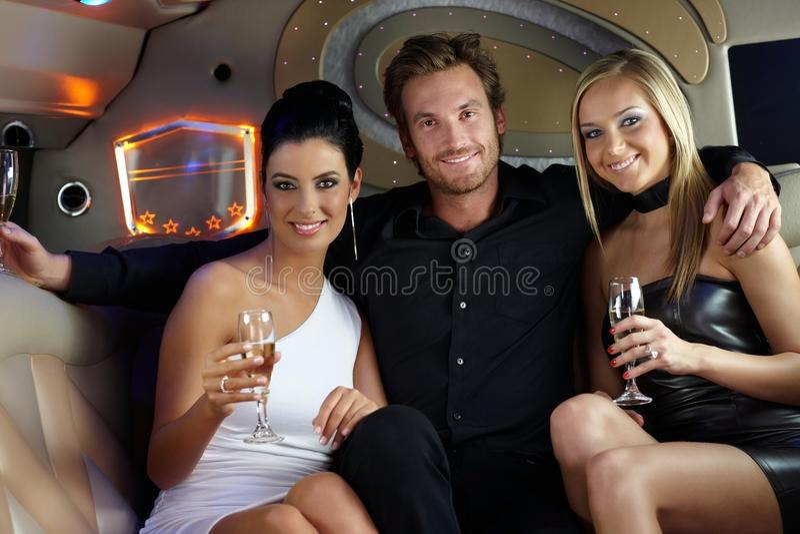 Les jeunes heureux dans la limousine image stock