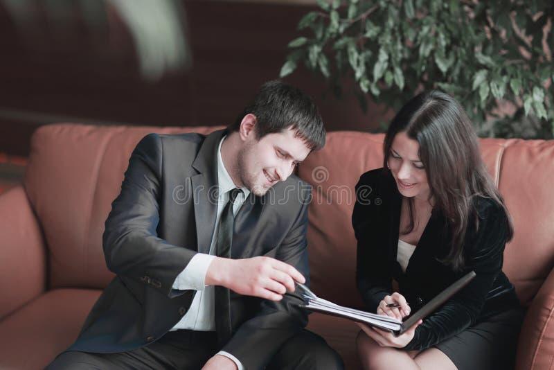 Les jeunes hommes d'affaires discutent le document d'entreprise se reposant sur le divan au centre d'affaires images stock