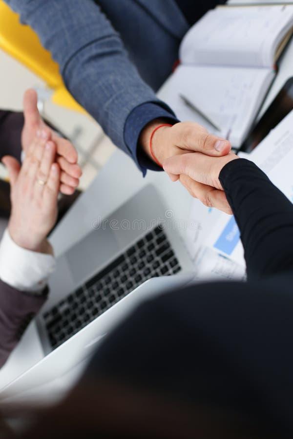 Les jeunes hommes d'affaires heureux font se serrer la main la réunion dans le bureau les uns avec les autres image libre de droits