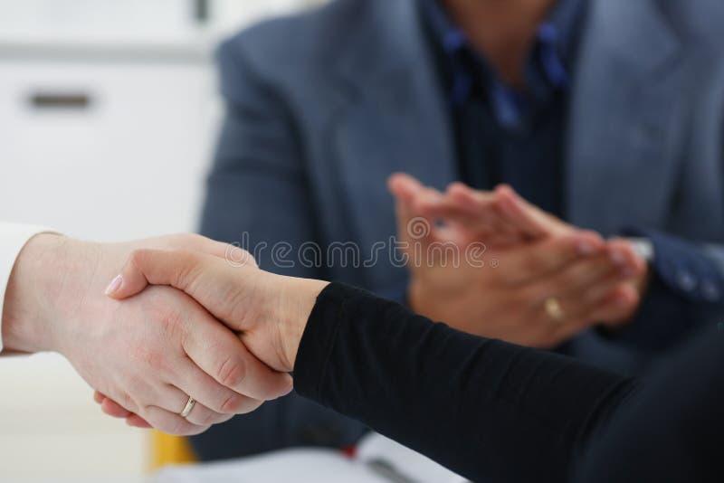 Les jeunes hommes d'affaires heureux font se serrer la main la réunion dans le bureau les uns avec les autres photos stock