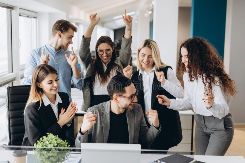 Les jeunes hommes d'affaires réussis soulèvent des mains dans des poings et crient avec bonheur tout en travaillant avec un ordin images libres de droits