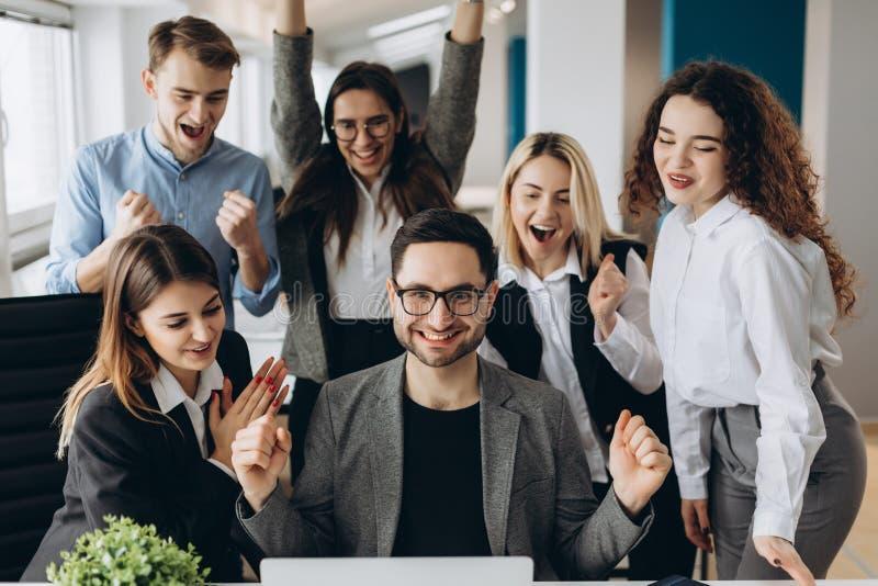 Les jeunes hommes d'affaires réussis soulèvent des mains dans des poings et crient avec bonheur tout en travaillant avec un ordin photographie stock