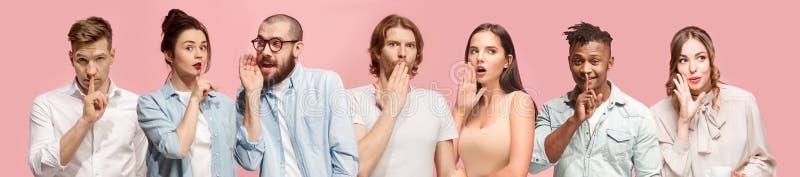 Les jeunes hommes et les femmes chuchotant un secret derrière remet le fond rose photos stock