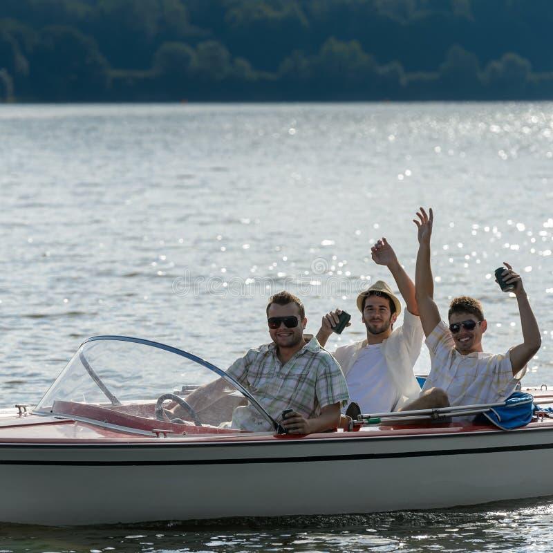 Les jeunes hommes gais boivent le bateau de vitesse de bière photo stock