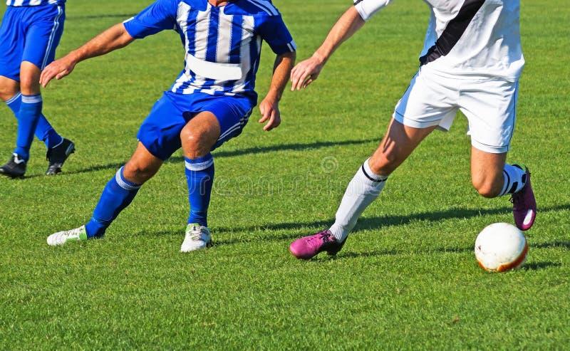 Les jeunes hommes jouent le football photographie stock libre de droits