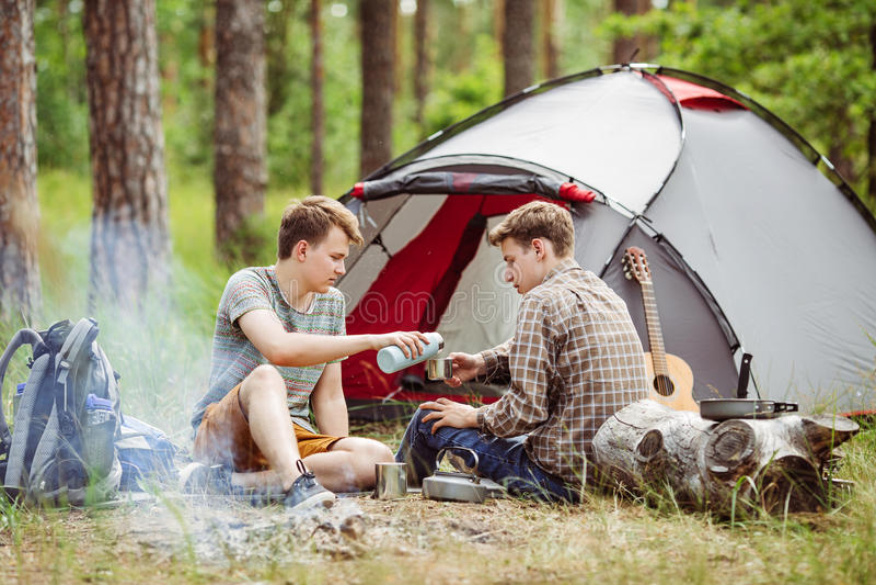 Les jeunes hommes sont passionnés dans un feu et un cuisinier sur une colonie de vacances photo stock