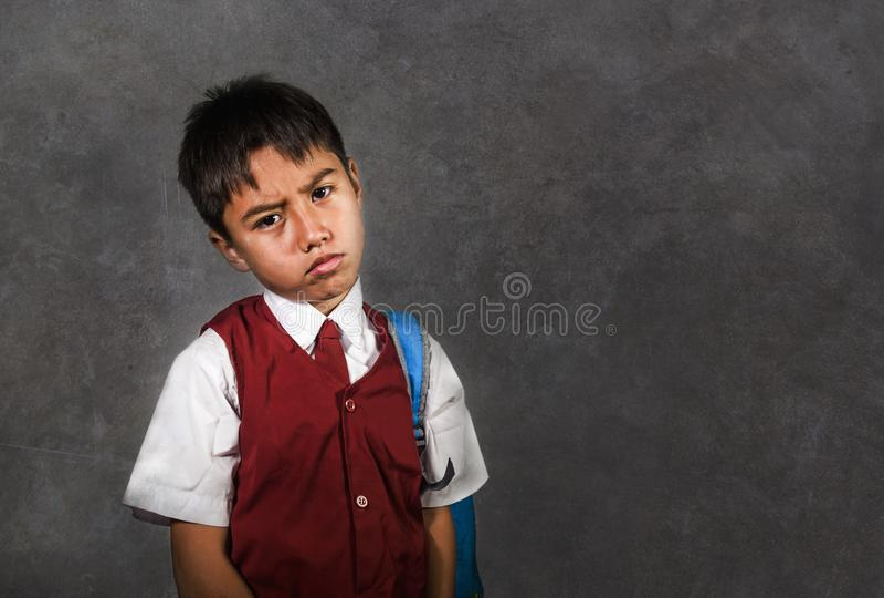 Les jeunes intimidés ont maltraité l'écolier dans déprimé triste de transport uniforme de sac d'école sur le tableau noir sentant photographie stock libre de droits