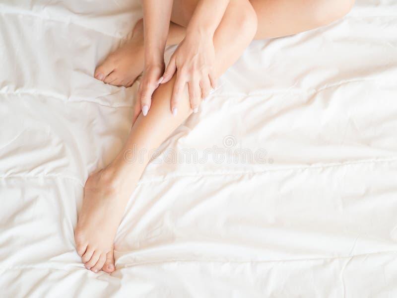 Les jeunes jambes femelles nues sexy se trouve sur le lit blanc couvert par la couverture photos stock