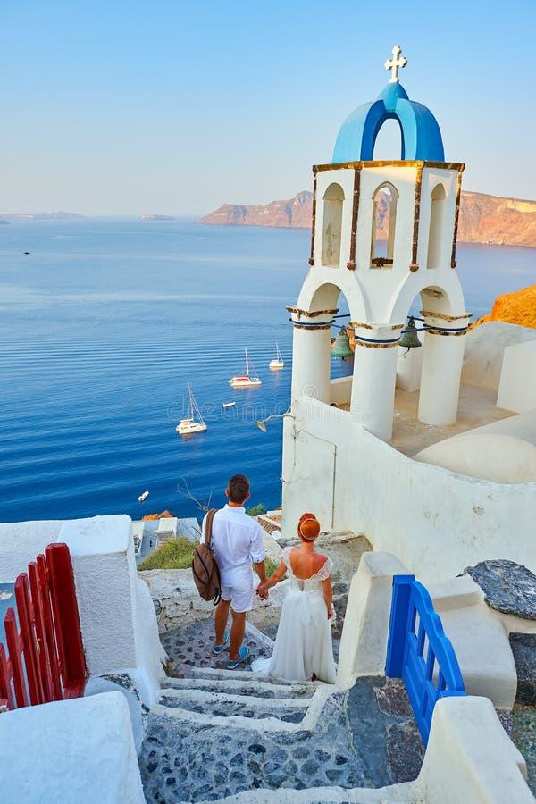 Les jeunes jeunes mariés de couples célèbrent le mariage sur Santorini image libre de droits