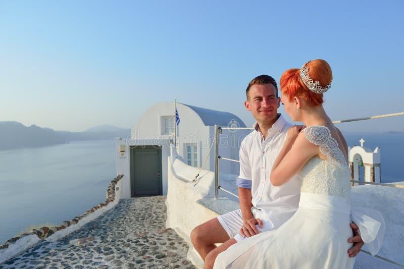 Les jeunes jeunes mariés de couples célèbrent le mariage sur Santorini images libres de droits