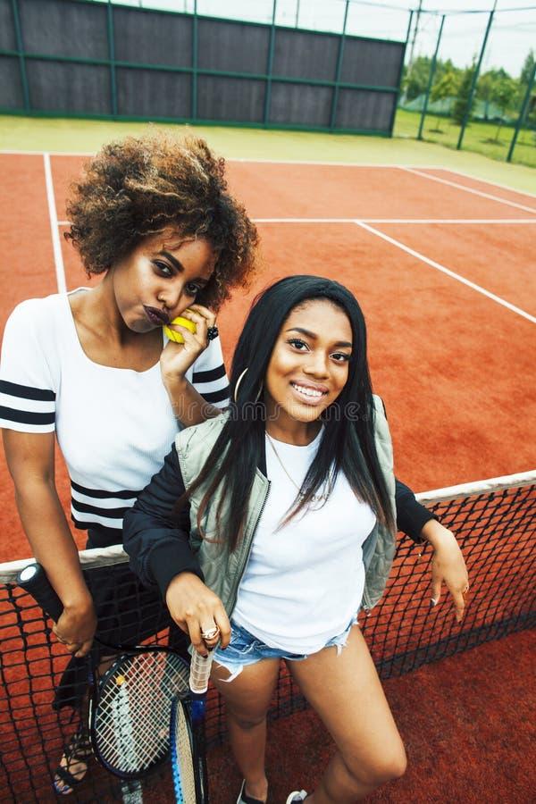Les jeunes jolies amies accrochant sur le court de tennis, fa?onnent le butin habill? ?l?gant, sourire heureux de meilleurs amis  photographie stock libre de droits