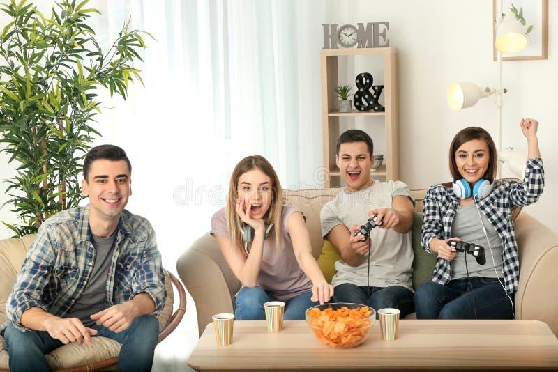 Les jeunes jouant des jeux vidéo à la maison photographie stock