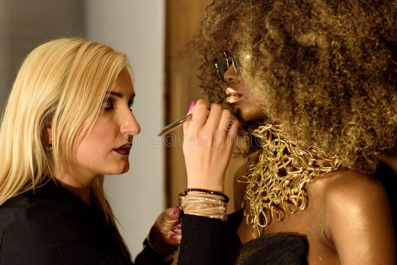 Les jeunes lèvres blondes d'or de peinture d'artiste avec le gland, façonnent le modèle américain africain ou noir photo libre de droits