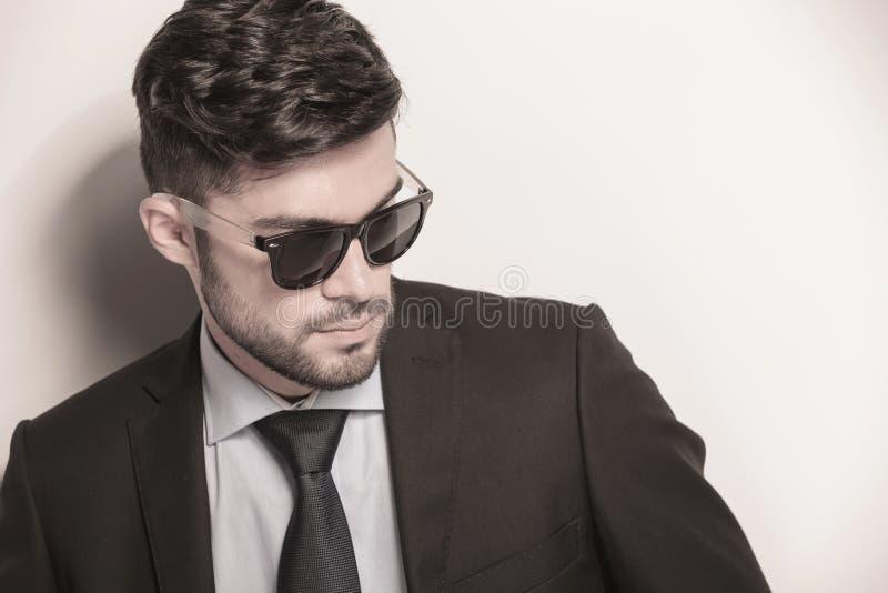 Les jeunes lunettes de soleil de port sexy d'homme d'affaires regardent loin image libre de droits