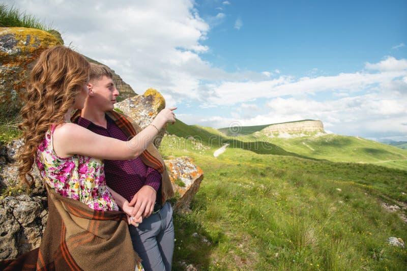 Les jeunes ménage sur le support de nature et tiennent des mains et la fille montre un doigt en direction d'un beau photographie stock libre de droits