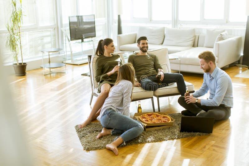 Les jeunes mangeant de la pizza et buvant du cidre dans l'intérieur moderne image stock