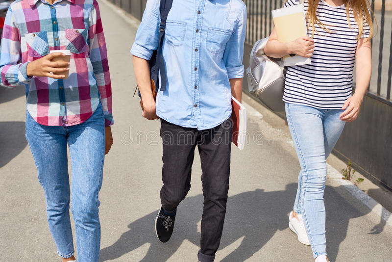 Les jeunes marchant à l'université photos stock