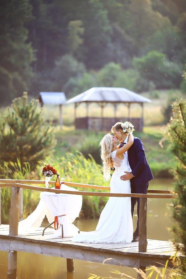 Les jeunes mariées embrassent Marche épousant des couples dans la forêt Foyer sélectif image stock