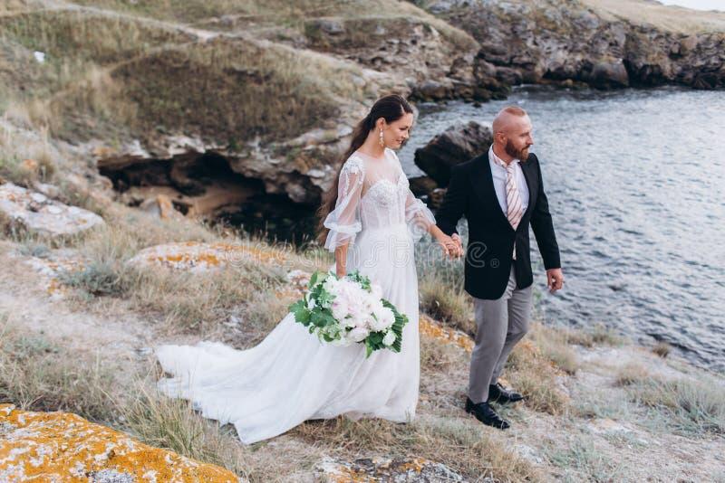 Les jeunes mariés étreignant et embrassant sur le fond de la mer et des roches photos stock