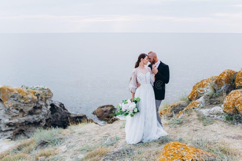 Les jeunes mariés étreignant et embrassant sur le fond de la mer et des roches images stock