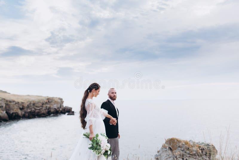 Les jeunes mariés étreignant et embrassant sur le fond de la mer et des roches image libre de droits