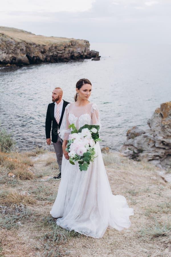 Les jeunes mariés étreignant et embrassant sur le fond de la mer et des roches photos libres de droits