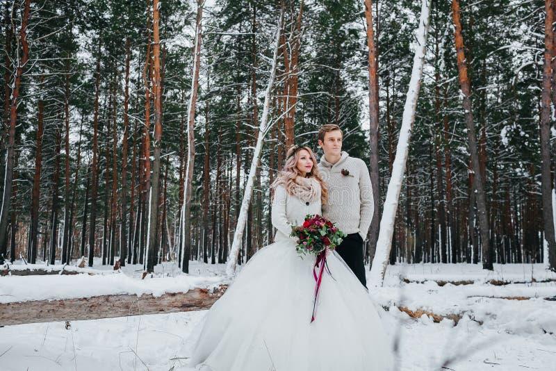 Les jeunes mariés avec un bouquet posent sur le fond du mariage neigeux d'hiver de forêt dessin-modèle photos libres de droits