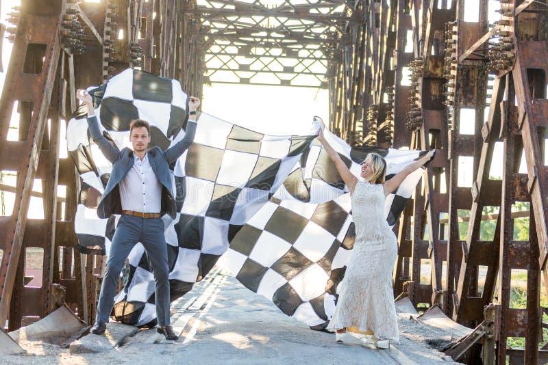 les jeunes mariés célèbrent leur lune de miel et soulèvent avec enthousiasme le drapeau noir et blanc sur le pont en fer joyeux photos libres de droits