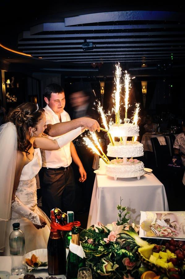 Les jeunes mariés coupant le gâteau à la cérémonie de célébration images stock