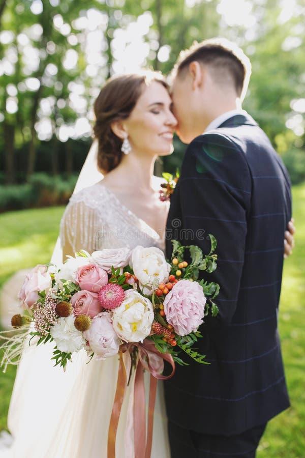 Les jeunes mariés heureux de nouveaux mariés de couples à un mariage en parc de vert de nature embrassent Jeune mariée avec le bo image libre de droits