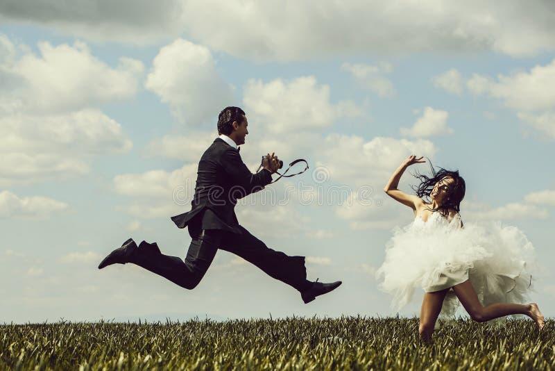 Les jeunes mariés heureux sautent photographie stock libre de droits