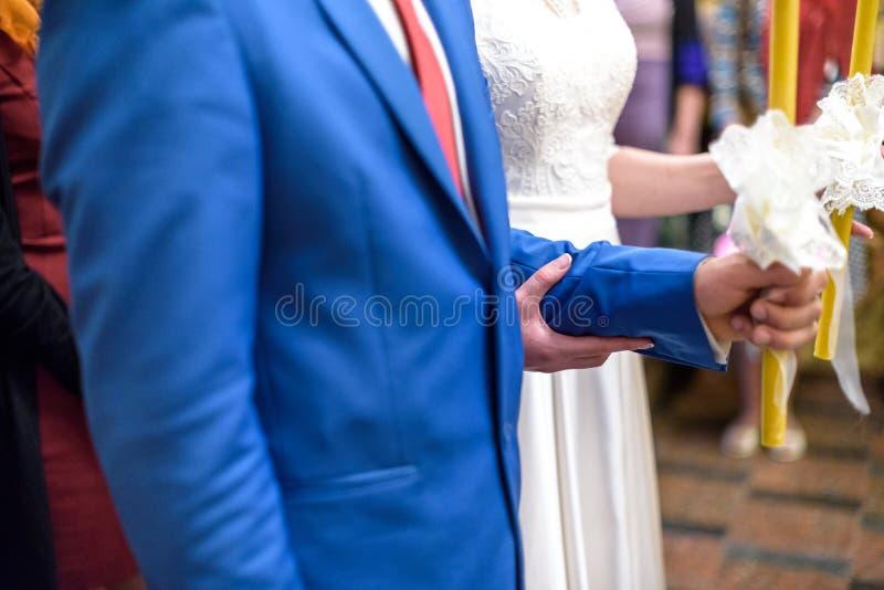 Les jeunes mariés jugent des bougies décorées des rubans de fleurs blanches photo libre de droits