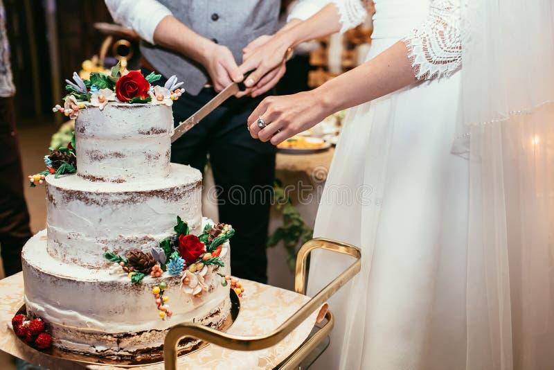 Les jeunes mariés ont coupé le gâteau de mariage rustique sur le banquet de mariage avec images stock