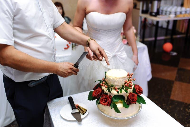 Les jeunes mariés ont coupé le gâteau l'épousant avec le couteau images stock