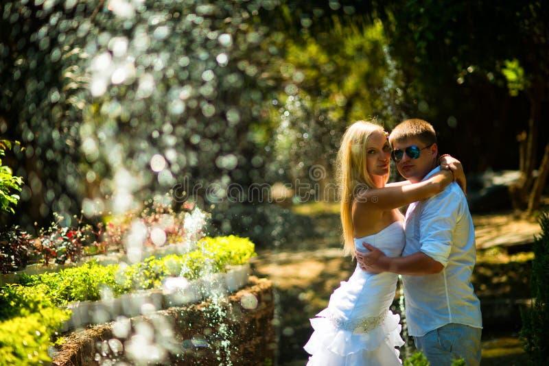 Les jeunes mariés posant au milieu de éclaboussent images stock