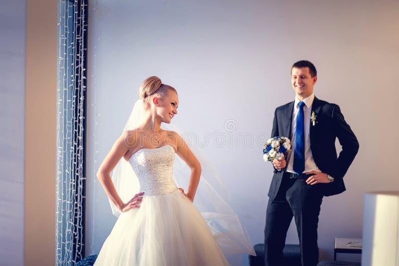 Les jeunes mariés posant dans une chambre d'hôtel avec l'intérieur blanc photos libres de droits