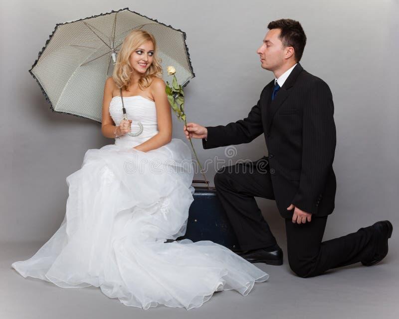 Les jeunes mariés romantiques de ménages mariés avec se sont levés image libre de droits