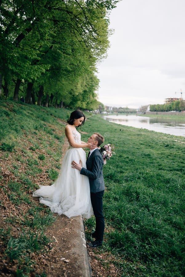 Les jeunes mariés s'étreindre Position sur la rue près de la rivière photographie stock libre de droits