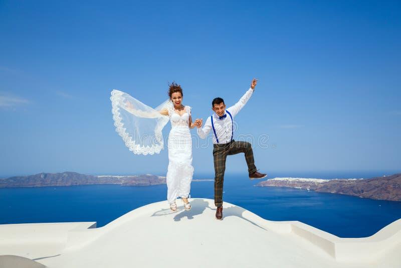 Les jeunes mariés sautent ensemble photographie stock libre de droits