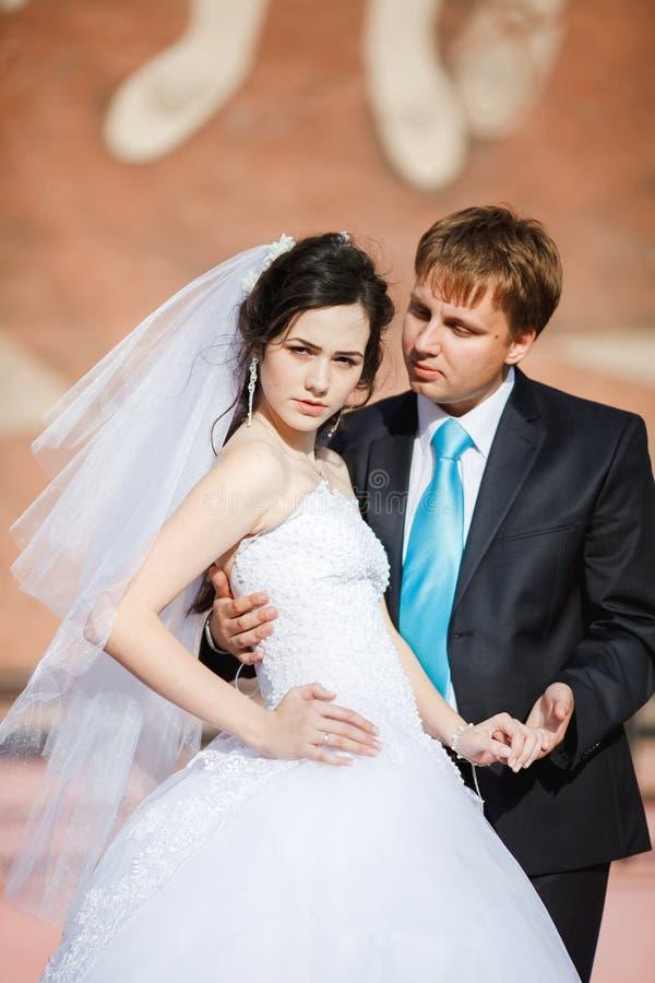 Les jeunes mariés se tenant ensemble posants avec photo libre de droits