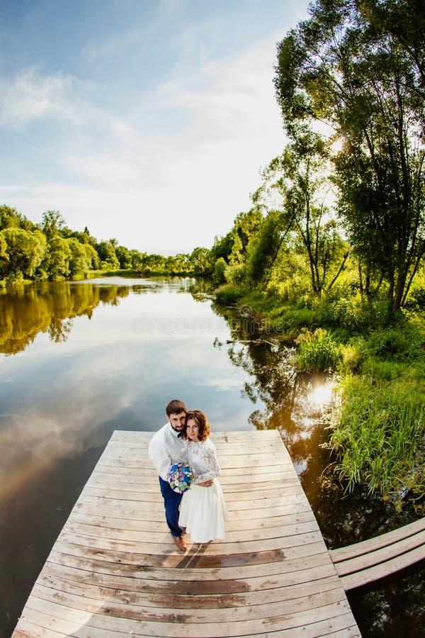 Les jeunes mariés se tiennent sur un pilier en bois près de l'étang images libres de droits