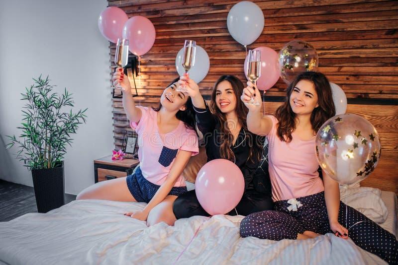 Les jeunes modèles gais se reposent sur le lit dans la chambre de fête Ils tiennent des verres avec le champaigne à l'air et au r images stock