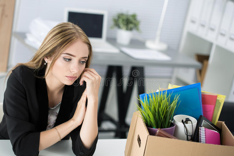 Les jeunes ont écarté le main-d'œuvre féminine dans le bureau se reposant près de la boîte de carton photos stock