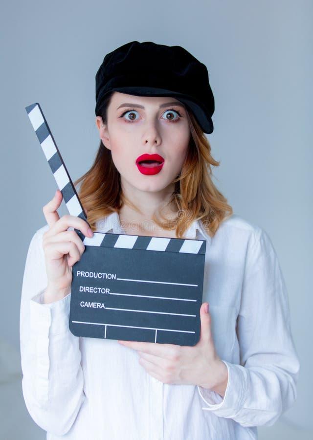 Les jeunes ont étonné la femme rousse dans le chapeau tenant le bardeau de film photo stock