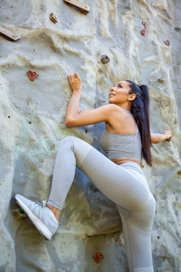 Les jeunes ont adapté bel s'élever de fille extérieur sur une roche artificielle photos stock
