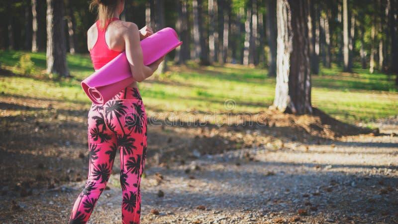 Les jeunes ont adapté la femme sportive dans une forêt utilisant la montre intelligente et tenant le tapis de yoga, marchant à pa photo libre de droits