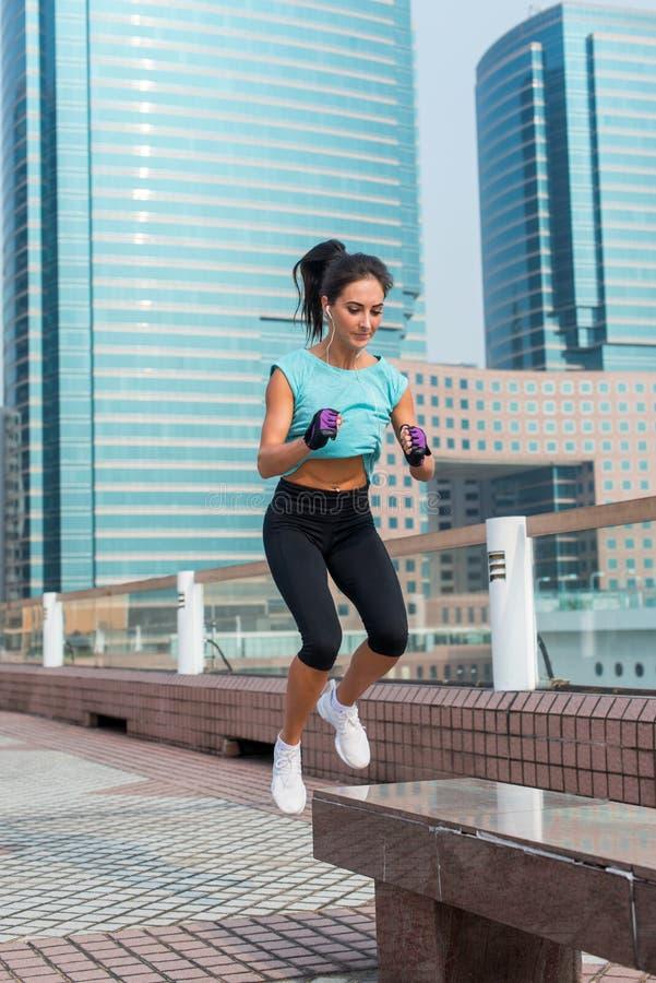 Les jeunes ont adapté sauter accroupi de femme de saut actif de banc sur la rue de ville Fille de forme physique faisant des exer image stock