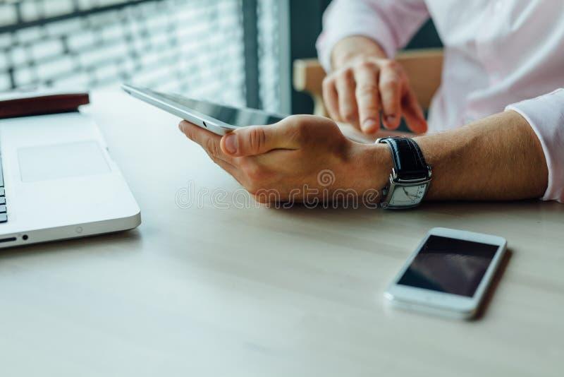 Les jeunes ont focalisé l'homme d'affaires s'asseyant en café avec l'ordinateur portable et le smartp photographie stock libre de droits