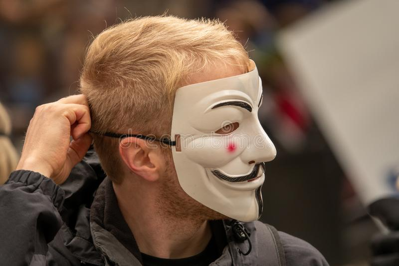 Les jeunes ont habillé tous dans le noir sortent sur la rue pour démontrer avec les masques anonymes image stock